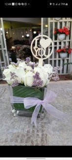 White roses in glass cube